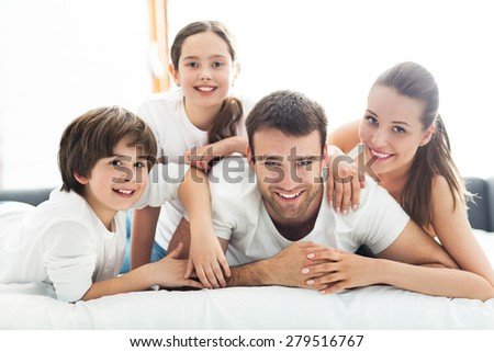 Family of four lying on bed - stock photo