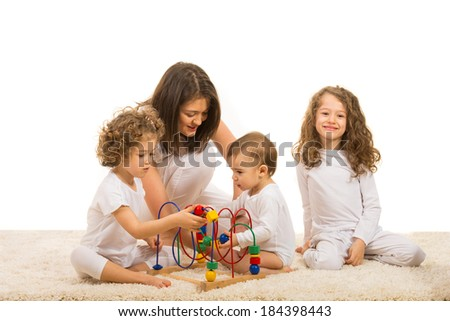 Family of four members playing  with wooden toy on carpet - stock photo