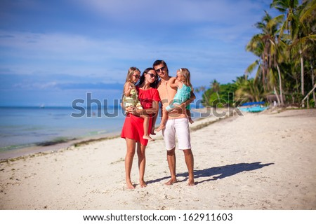 Family of four on beach vacation - stock photo