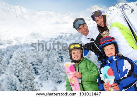 Family of four people at the mountain in winter - stock photo