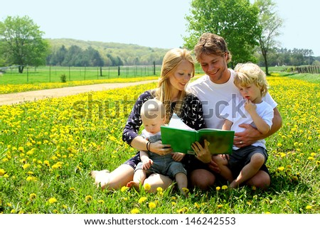 Family of four people including mother, father, baby, and little child are sitting outside in a field of dandelion flowers, reading a story - stock photo
