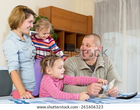 family of four planning budget and smiling indoors. Focus on man - stock photo