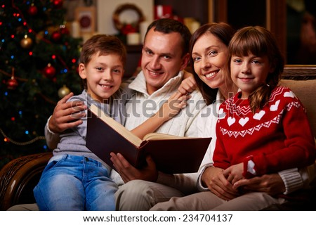 Family of four reading tales on Christmas evening - stock photo
