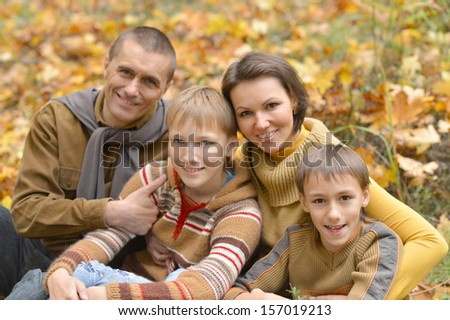Family of four sitting on ground in autumn forest - stock photo