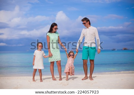 Family of four walking by the sea and enjoy beach vacation - stock photo
