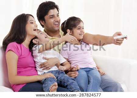 Family of four watching television - stock photo