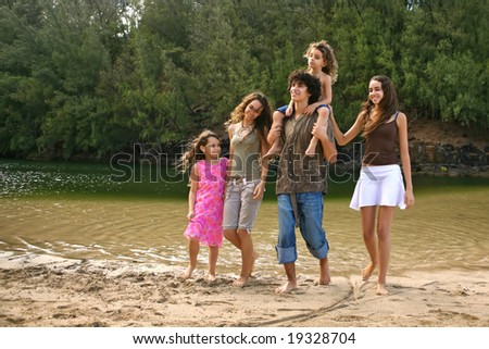 Family of 5 Happy Children Walking Along the Beach - stock photo