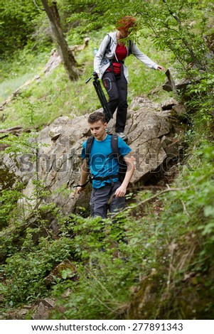 Family of hikers on a mountain trail in a sunny spring day - stock photo