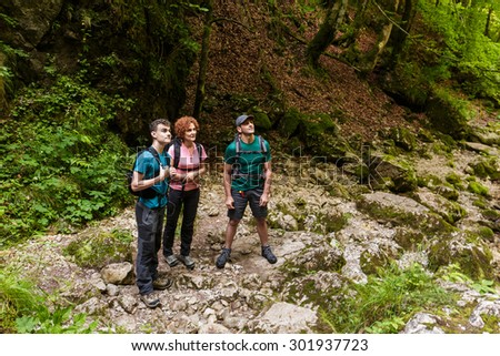 Family of hikers standing in the forest and looking up - stock photo