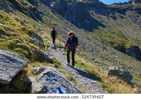 Family of hikers with backpacks on a trail in rocky mountains - stock photo