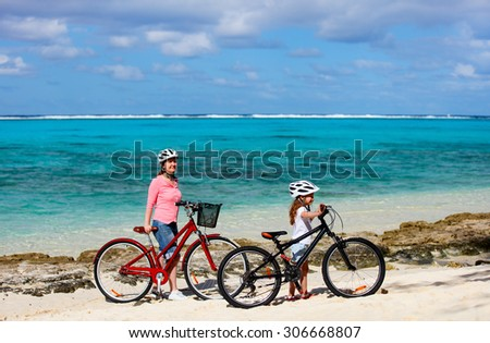 Family of mother and daughter biking at tropical beach having fun together - stock photo