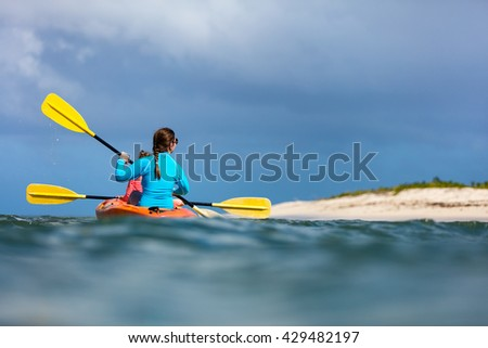 Family of mother and daughter paddling on kayaks at tropical ocean water during summer vacation - stock photo