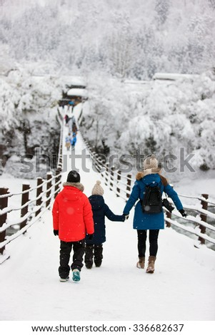 Family of mother and kids crossing the bridge over Shogawa river at historic Japanese village Shirakawa-go at winter, one of Japan's UNESCO world heritage sites - stock photo
