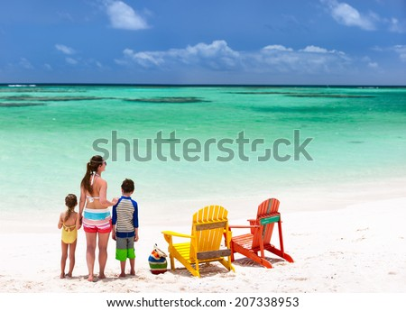 Family of mother and kids enjoying vacation at tropical beach with two colorful wooden chairs on white sand and turquoise ocean water in Caribbean - stock photo