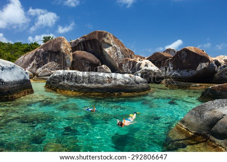 Family of mother and son snorkeling in turquoise tropical water among huge granite boulders at The Baths beach area major tourist attraction on Virgin Gorda, British Virgin Islands, Caribbean - stock photo