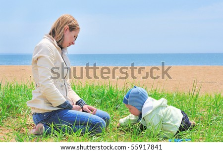 family of mother playing with baby on the sand sea beach - stock photo