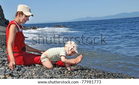 family of mother with baby on the sea beach - stock photo