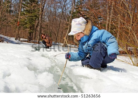 family of mother with kid playing in the  snow  spring forest stream - stock photo