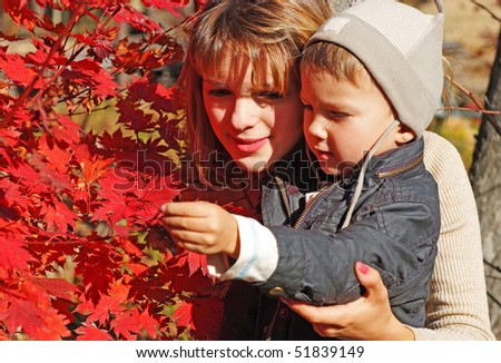 family of mother with kid teaching botany  in the fall forest - stock photo