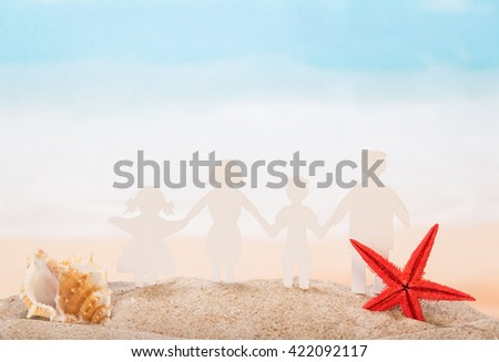 Family of paper, seashell and star in the sand against the sea. - stock photo