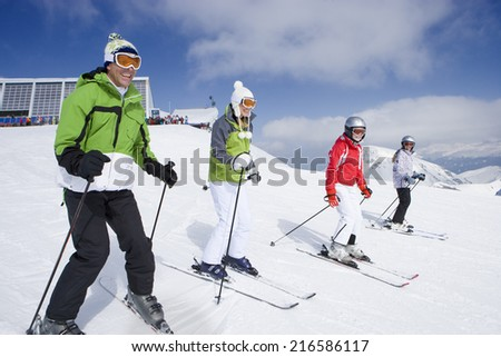 Family of skiers skiing downhill on ski slope - stock photo