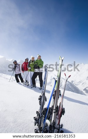 Family of skiers smiling together on mountain top - stock photo