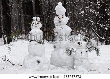 Family of snowmen in a pine forest - stock photo