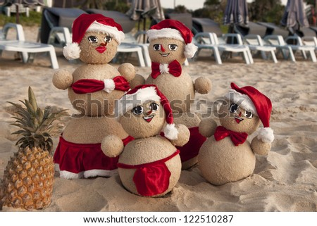Family of snowmen on the beach in xmas outfits with smiling faces - stock photo