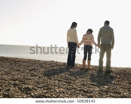 Family of three holding hands, standing on beach, back view - stock photo