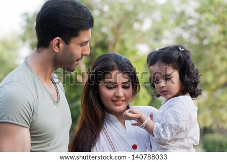 family of three in outdoor, young couple with daughter in the outdoors. - stock photo