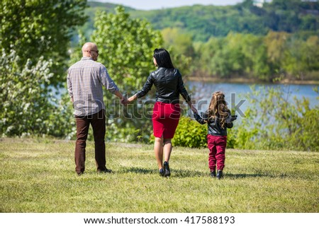Family of three members walking in the park near river - stock photo