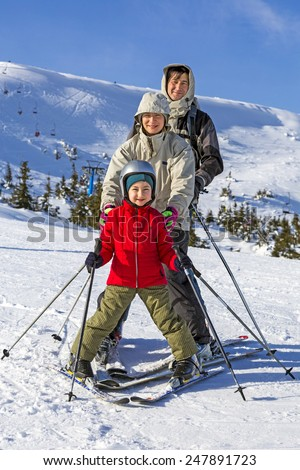 Family of three people learns skiing together. Happy, smiling, joyful - stock photo
