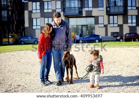 Family of three person with toddler boy and dog playing near the city house - stock photo
