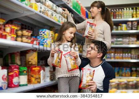Family of three purchasing food for week at supermarket. Focus on man - stock photo