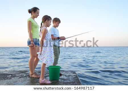 Family of three with a fishing rod fishing in the sea - stock photo