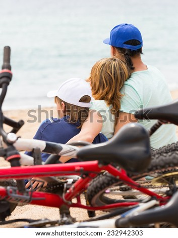 Family of three with bicycles behind in vacation at seashore - stock photo