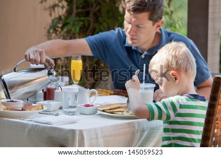 family of two eating nicely served breakfast outside; handsome young man pouring some coffee and his cute son eating delicious pancakes at breakfast time - stock photo