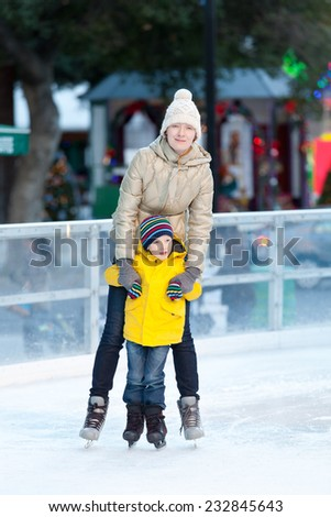 family of two ice skating together - stock photo
