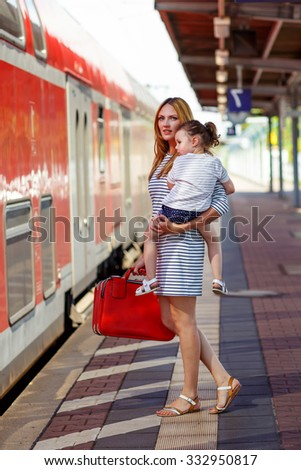 Family of two: little toddler girl and her mum on a railway station. Kid and woman waiting for train and happy about a journey. People, travel, family, lifestyle concept - stock photo