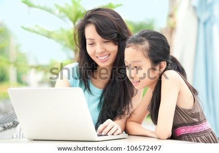 Family of two using laptop outdoors - stock photo