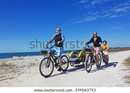Family on a beach bicycle ride together - stock photo