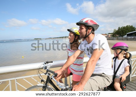 Family on a biking journey by the sea - stock photo