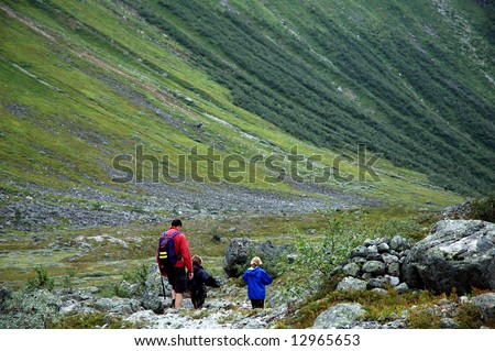 family on a hike in the mountains - stock photo
