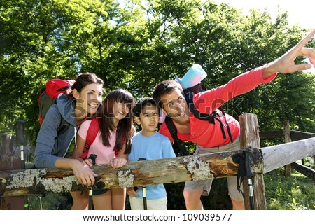 Family on a hiking day resting along fence - stock photo