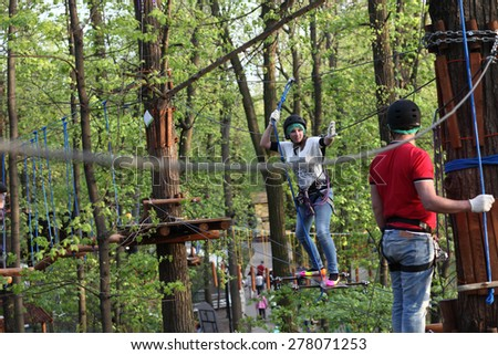 Family on a rope climbing in the adventure park - stock photo