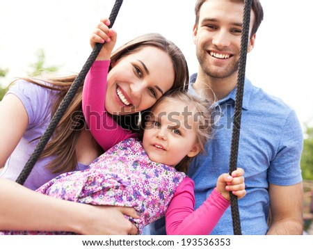 Family on a swing - stock photo
