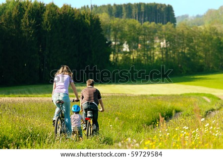 Family on a trip with their bicycles in a wonderful scenery, since their son is so young he is riding a training bike - stock photo