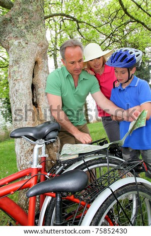 Family on bicycle ride looking at map - stock photo