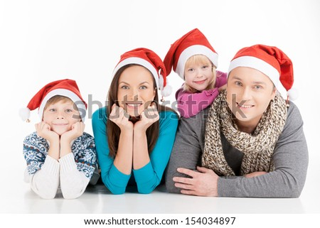 Family on Christmas. Cheerful family in Santa hats looking at camera and smiling while isolated on white - stock photo