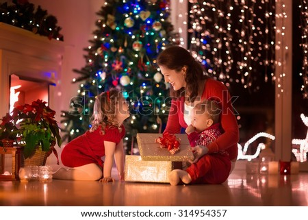 Family on Christmas eve at fireplace. Mother and little kids opening Xmas presents. Children with gift boxes. Living room with traditional fire place and decorated tree. Cozy winter evening at home. - stock photo